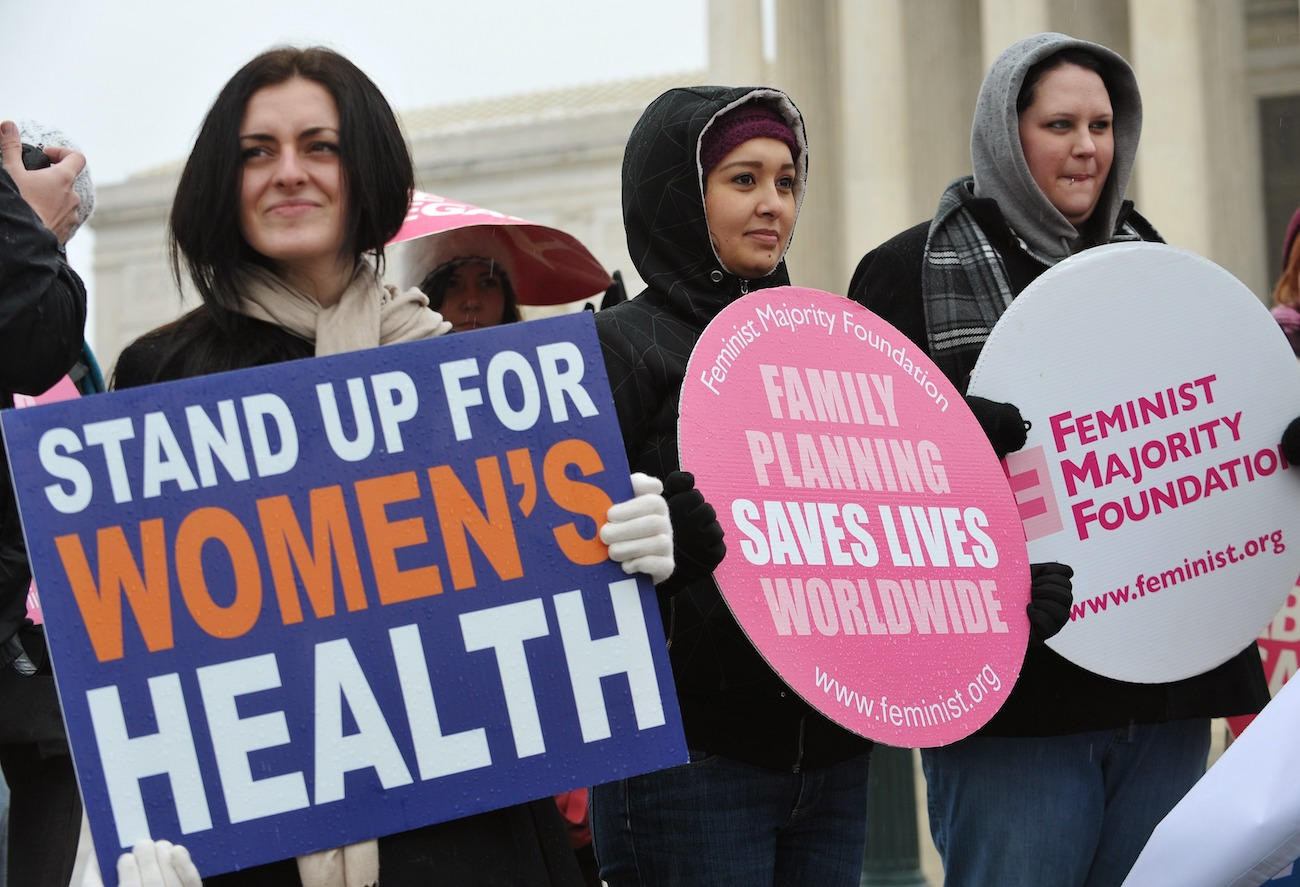 """Pro-choice activists hold placards during a rally, one of which reads """"Stand up for women's health"""""""