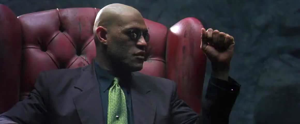 Morpheus (Laurence Fishburne) explaining the history of the war against the Machines to Neo (Keanu Reeves, not pictured) in a chair in the desert in The Matrix.