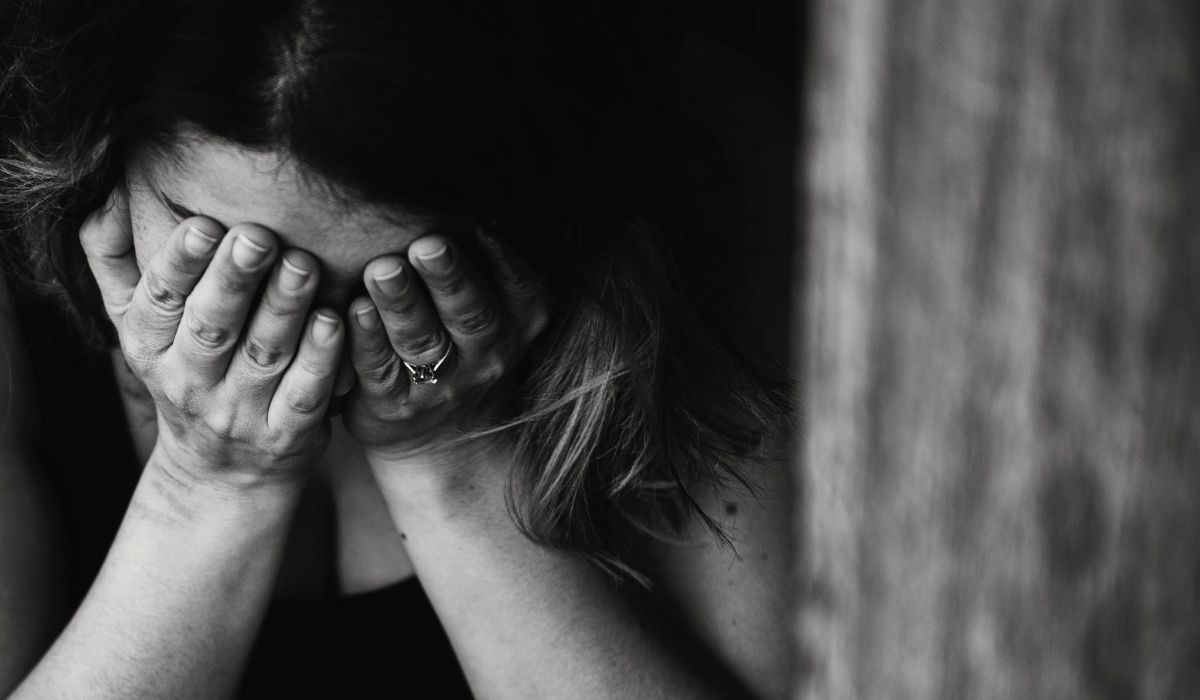 Black and white image of someone crying into their hands. (Image: Kat Jayne on Pexels.)