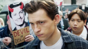 Tom Holland as Peter Parker walking through a protest that says Devil in Disguise