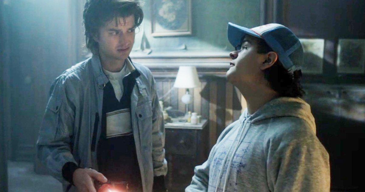 Steve Harrington and Dustin staring at each other in a haunted house in Stranger Things