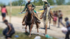 Slightly blurred image of federal agents on horses near the Rio Grande corralling Haitian refugees. (Image: John Moore/Getty Images.)