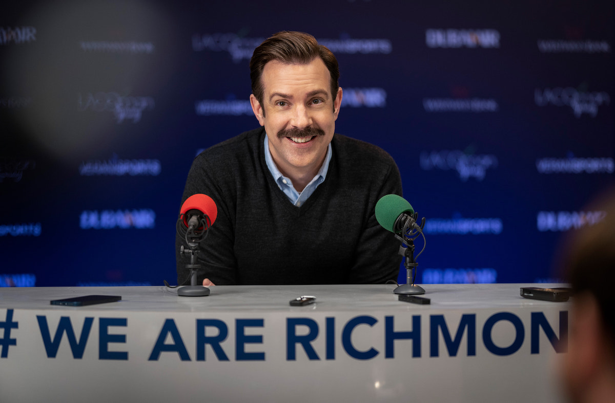 Ted Lasso smiles during a press conference in an episode of Ted Lasso