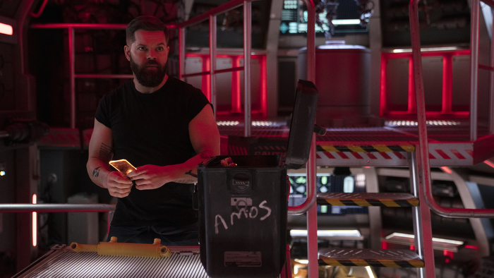 Wes Chatham stands beside a box labeled 'Amos' on the Rocinante ship as Amos in 'The Expanse' season six