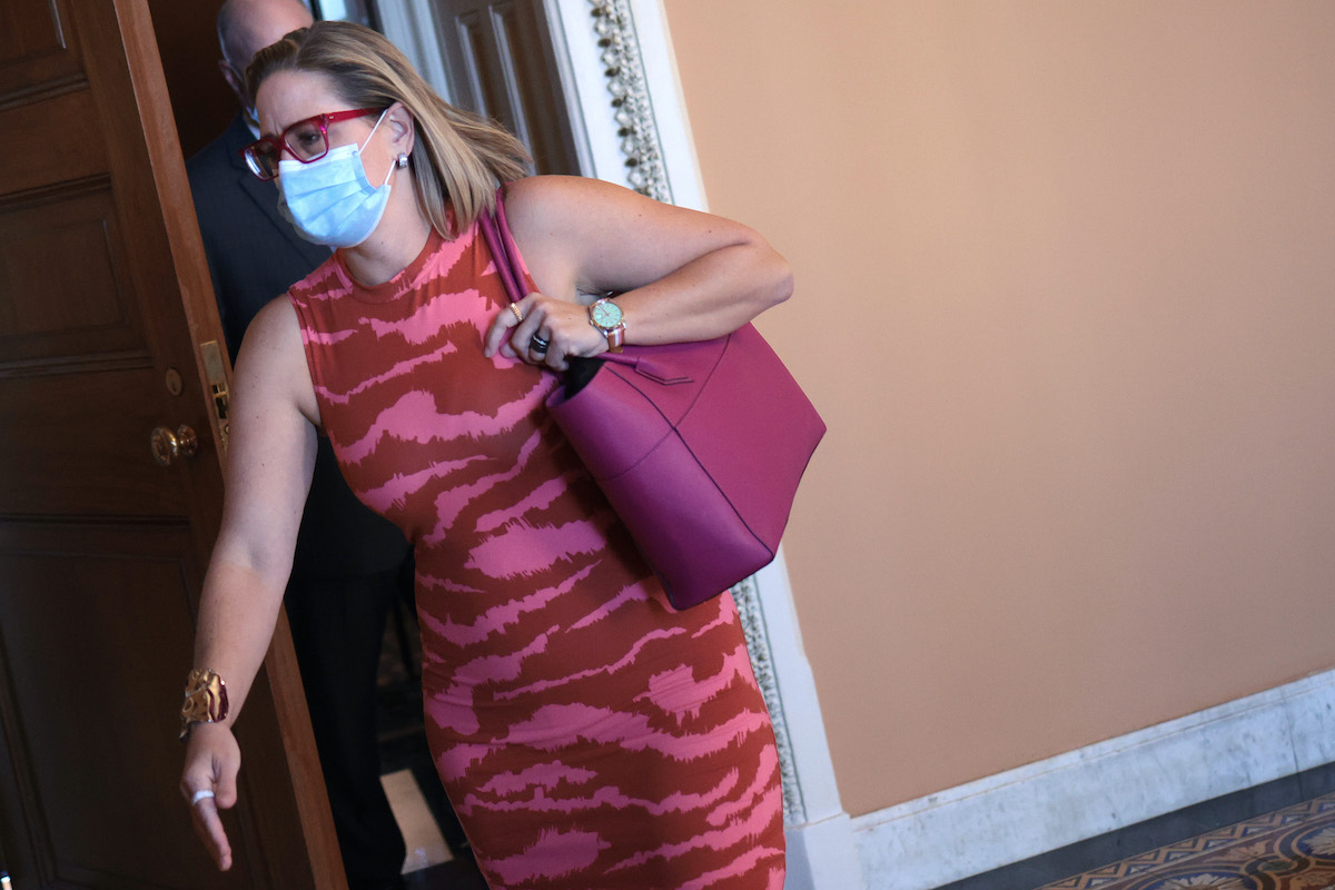 Kyrsten SInema dressed in a bright pink dress, rushes through the Capitol
