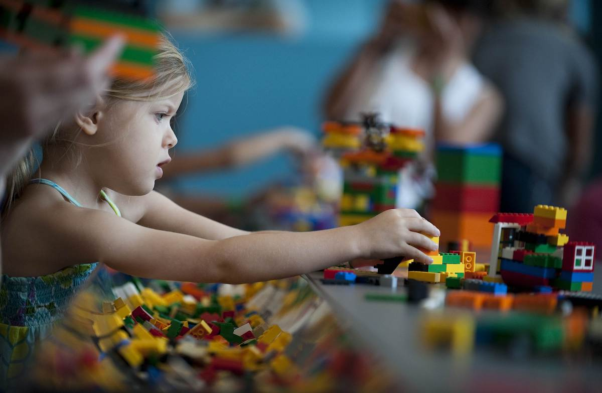 A young child plays with Lego building blocks